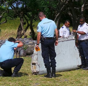 French gendarmes and police inspect a large piece of plane debris which was found on the beach in Saint-Andre