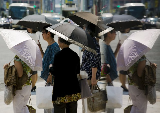 Women hold parasols as they wait at a pedestrian crossing on a hot day in Tokyo