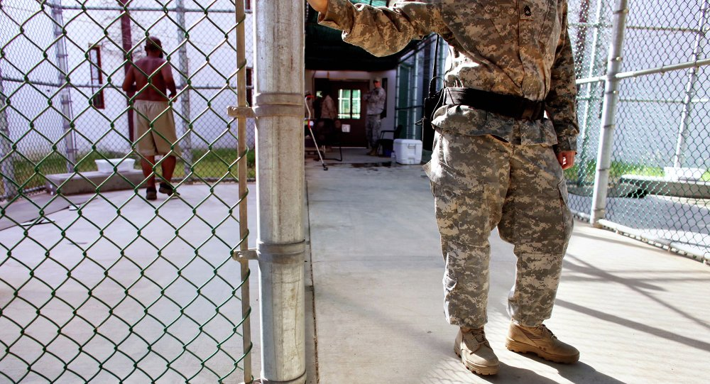 In this photo, reviewed by the US Military, a guard leans on a fencepost as a Guantanamo detainee, left, jogs inside the exercise yard at Camp 5 detention center, the U.S. Naval Base, in Guantanamo Bay, Cuba, January 21, 2009