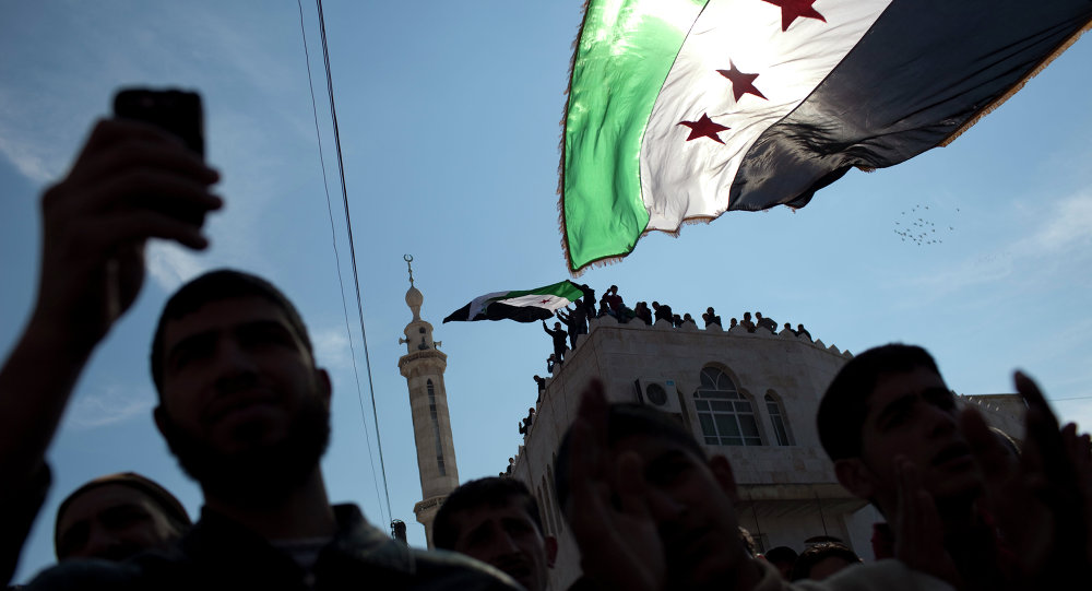 Men hold revolutionary Syrian flags during an anti-government protest in a town in northern Syria