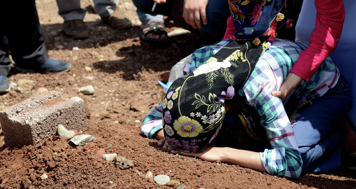 A woman mourns over the grave of a Kurdish fighter