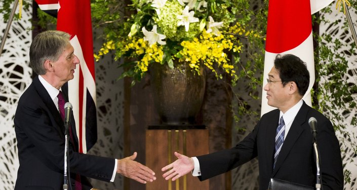 Japan's Foreign Minister Fumio Kishida (R) shakes hands with British Foreign Secretary Philip Hammond after a news conference about the 4th UK-Japan Strategic Dialogue at Iikura House in Tokyo