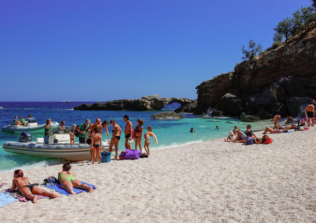 Tourists sunbathing at the beach of Cala Luna, Gulf of Orosei, Sardinia, Italy.