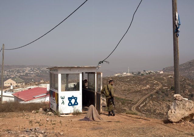 Israeli soldiers stand guard at their position at the West Bank Israeli outpost of Achiya, near the Palestinian village of Jalud Duma (background), on August 4, 2015, a week after the house of a Palestinian Dawabsha family was set on fire by suspected Jewish extremists, killing 18-month-old Ali Saad Dawabsha and critically injuring his parents and four-year-old brother