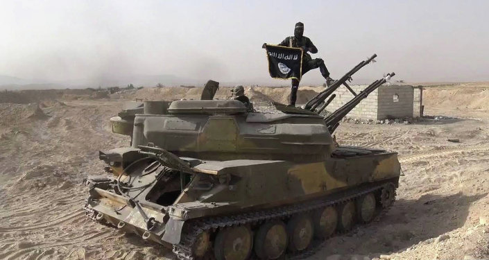 In this picture released on Wednesday, Aug. 5, 2015 by the Rased News Network a Facebook page affiliated with Islamic State militants, an Islamic State militant holds the group's flag as he stands on a tank they captured from Syrian government forces, in the town of Qaryatain southwest of Palmyra, central Syri