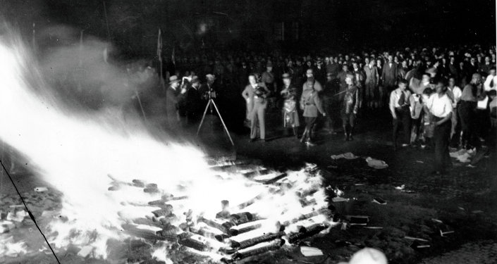 Flames roar high as a crowd gathers to witness thousands of books, considered to be un-German, burn in Opera Square in Berlin, Germany, during the Buecherverbrennung, book burnings on May 10, 1933.
