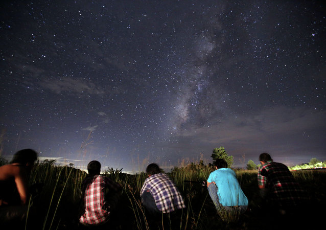 This long-exposure photograph taken on August 12, 2013 shows people watching for the Perseid meteor shower in the night sky