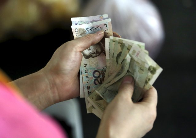 A customer counts Chinese Yuan notes at a market in Beijing, August 12, 2015