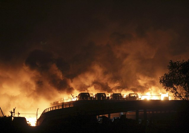 Vehicles are seen burning after blasts at Binhai new district in Tianjin municipality, China, August 13, 2015