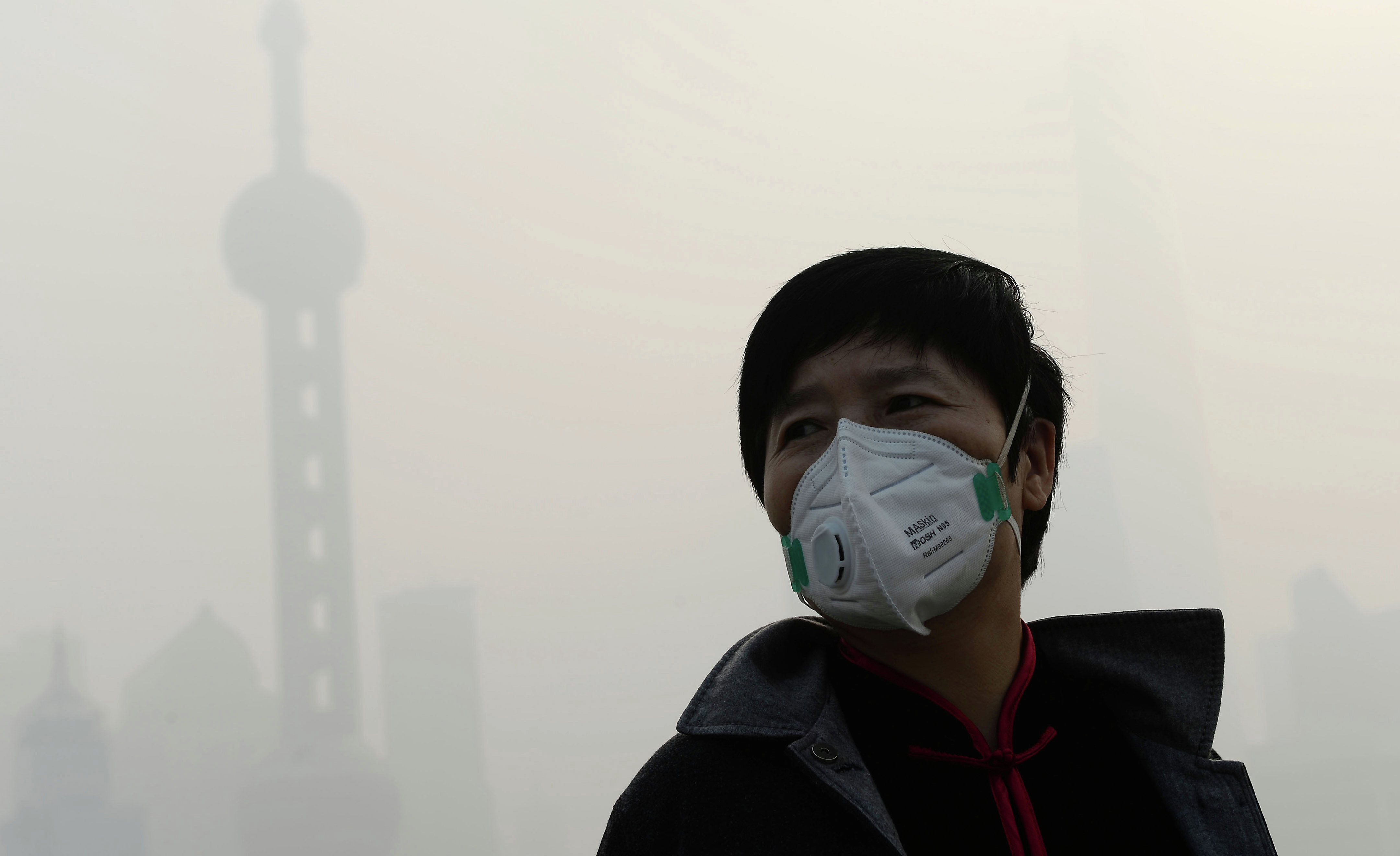 A man wearing a mask amid heavy smog on the Bund in Shanghai as local meteorological department issued a yellow alert for smog