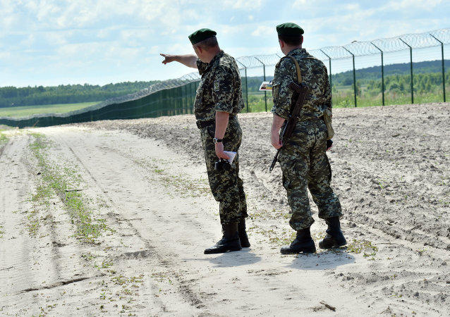 Ukrainian border guards patrol on July 2, 2015 along the barbed wire fence on the Senkivka border post, around 200 kilometres (125 miles) north of the Ukrainian capital Kiev.