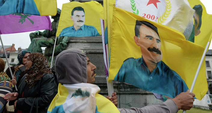 Demonstrators wave flags bearing pictures of jailed Kurdish rebel leader Abdullah Ocalan during a protest against the Turkish government in Brussels on July 28, 2015