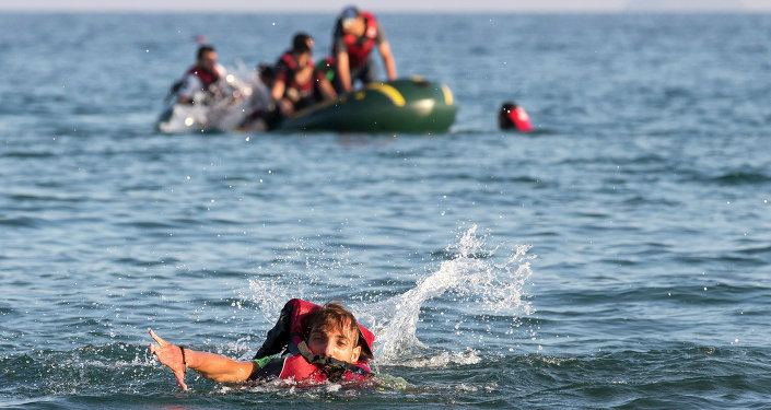 Migrants and refugees, one of them swims, arrive after crossing from Turkey, at the southeastern island of Kos, Greece, Monday, Aug. 17, 2015