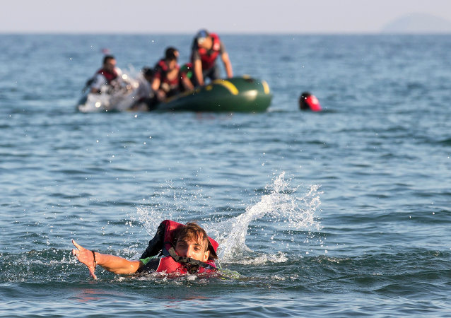 Migrants and refugees, one of them swims, arrive after crossing from Turkey, at the southeastern island of Kos, Greece, Monday, August 17, 2015.