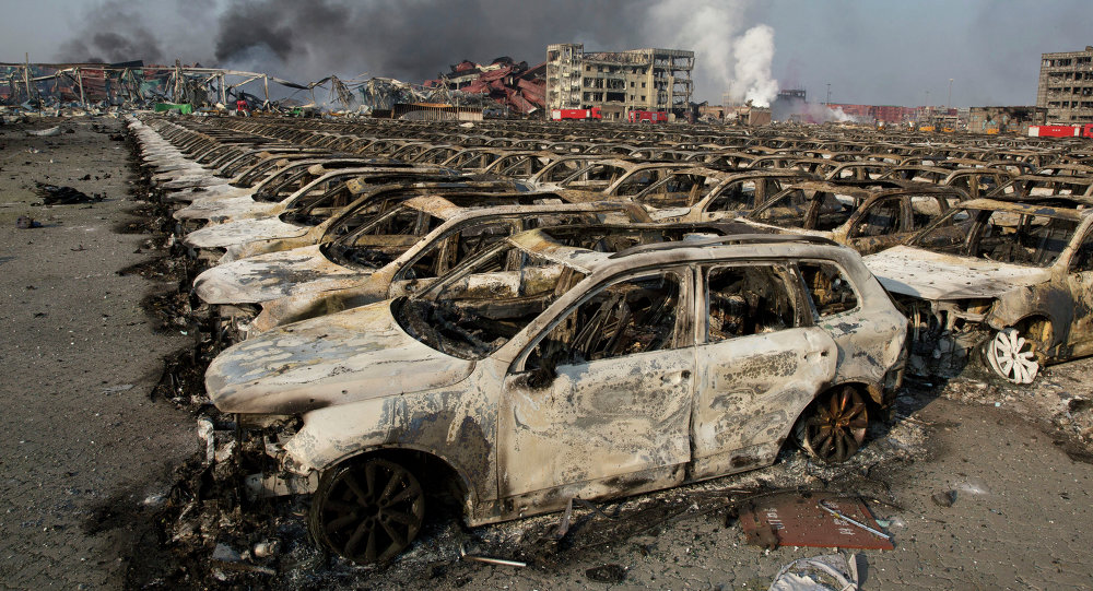 Smoke billows from the site of an explosion that reduced a parking lot filled with new cars to charred remains at a warehouse in northeastern China's Tianjin municipality, Thursday, Aug. 13, 2015