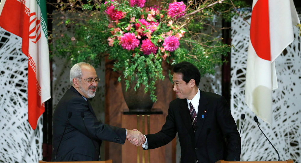 Iranian Foreign Minister Mohammad Javad Zarif, left, shakes hands with his Japanese counterpart Fumio Kishida.