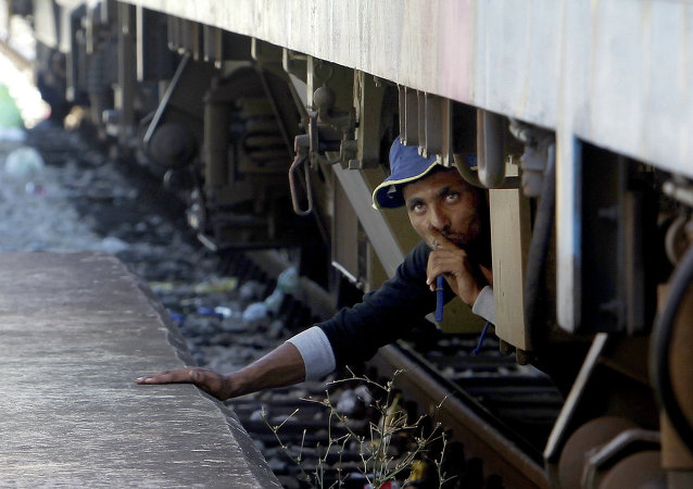 A migrant, hiding under a train, tries to sneak on a train towards Serbia, at the railway station in the southern Macedonian town of Gevgelija, on Monday, Aug. 17, 2015