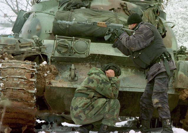 A Yugoslav special forces policeman shoots his rifle at opposing Kosovo Liberation Army forces as a Yugoslav Army tank driver covers his ears after coming under fire Tuesday Feb. 23, 1999 in the village of Bukos