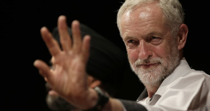 British lawmaker Jeremy Corbyn waves to a member of the audience prior to addressing a meeting during his election campaign for the leadership of the British Labour Party in Ealing, west London, Monday, Aug. 17, 2015