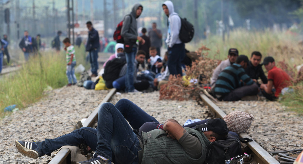 Migrants rest while waiting to pass the Greek-Macedonian border, guarded by Macedonian police near the town of Idomeni, northern Greece, on August 21, 2015