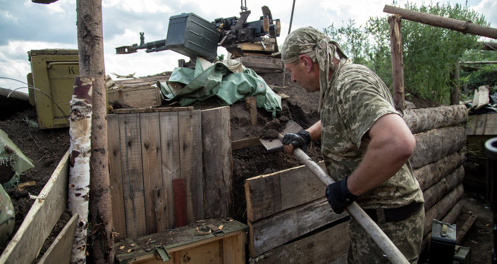 A serviceman strengthens the trench on the position of Ukrainian forces near airport of Donetsk on August 19, 2015