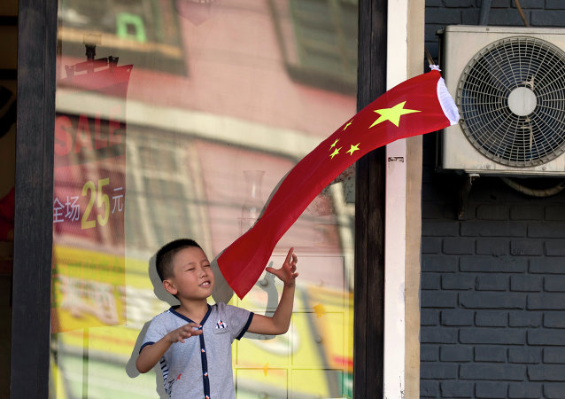 A child plays with a Chinese national flag near an area cordoned off for rehearsals ahead of a military parade to commemorate the end of World War II in Beijing, Saturday, Aug. 22, 2015