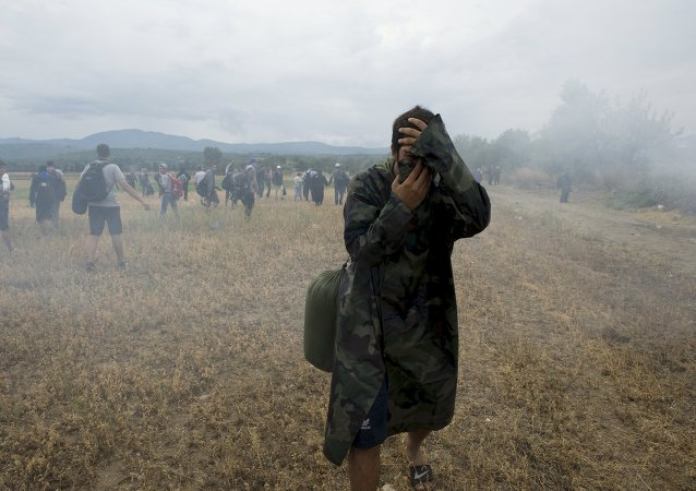 A migrant covers his face to avoid inhaling tear gas while others flee, as Macedonian police special forces block them from entering Macedonia on Greece's, near the village of Idomeni, Greece, August 22, 2015.