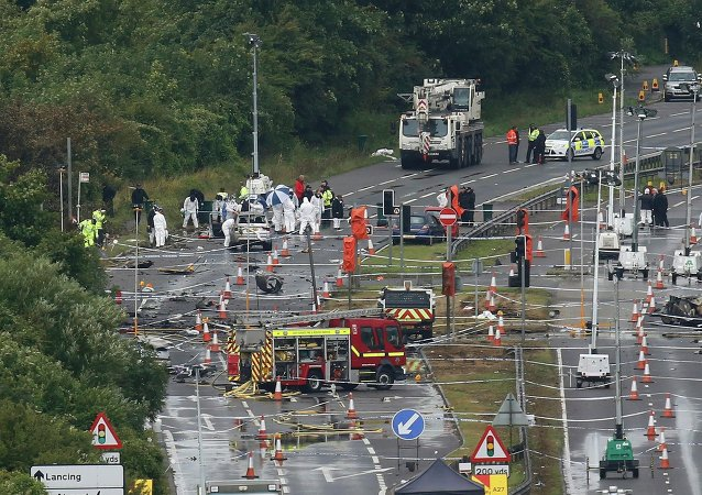 A crane arrives on site as emergency services and crash investigation officers continue to work at the site where a Hawker Hunter fighter jet crashed onto the A27 road at Shoreham near Brighton, Britain