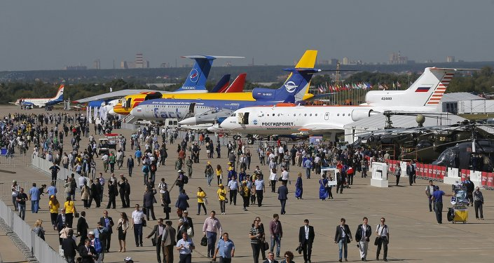 Visitors walk along a row of planes and helicopters on display at the MAKS International Aviation and Space Salon