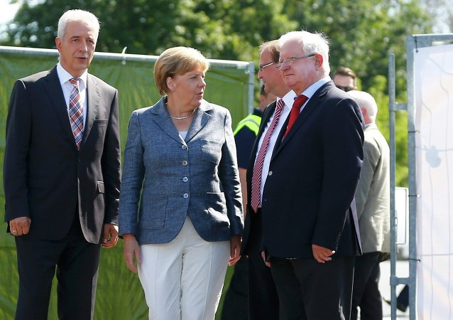 Saxony State Prime Minister Stanislaw Tillich, German Chancellor Angela Merkel, major Juergen Opitz and President of the German Red Cross Rudolf Seiters (LtoR) arrive to visit an asylum seekers accomodation facility in the eastern German town of Heidenau near Dresden, August 26, 2015 where last week more than 30 police were injured in clashes, when a mob of several hundred people pelted officers with bottles and fireworks