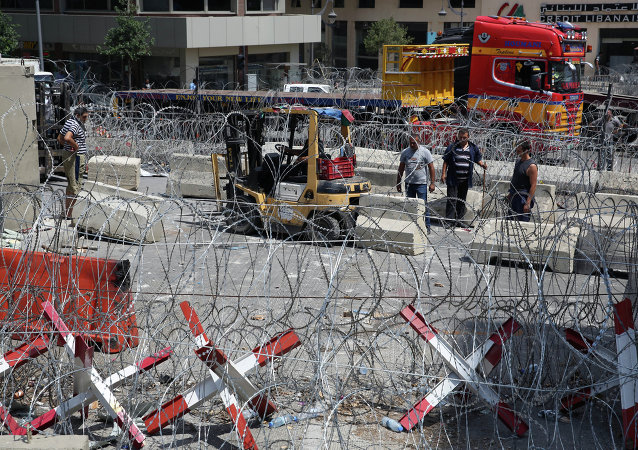 A Lebanese engineering unit install barriers after they remove a concrete wall that was installed by authorities, near the main Lebanese government building, in downtown Beirut, Lebanon, Wednesday, Aug. 26, 2015