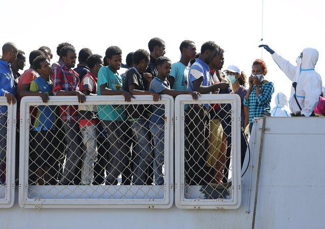 Migrants wait to disembark from an Italian navy vessel in the Sicilian harbour of Augusta, Italy, August 23, 2015