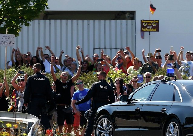 People hold a placard reading Traitor as German Chancellor Angela Merkel leaves after her visit to an asylum seekers accomodation facility in the eastern German town of Heidenau near Dresden, August 26, 2015 where last week more than 30 police were injured in clashes, when a mob of several hundred people pelted officers with bottles and fireworks