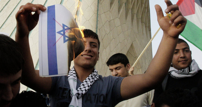 An Iranian demonstrator burns a representation of the Israeli flag with red lines indicating cancellation, in a pro-Palestinian demonstration in Tehran, Iran