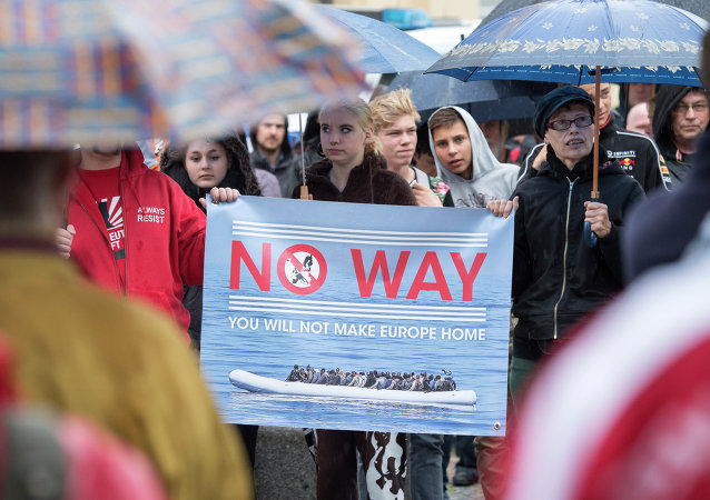 People take part at a demonstration initiated by right-wing NPD (National Democratic Party of Germany) against the German asylum law and asylum seekers in Riesa, eastern Germany, Tuesday, Aug. 18, 2015