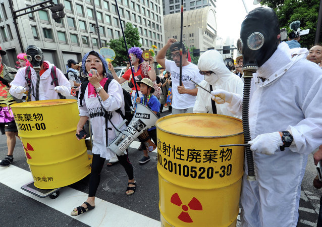 Protesters wearing gas masks and white costumes similar to those of decontamination workers at the crippled Fukushima plant beat drums painted with radioactive waste symbols during an anti nuclear power demonstration march in Tokyo on July 29, 2012