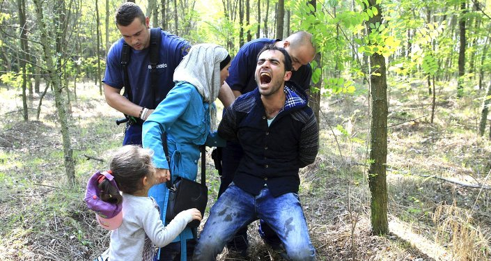 Hungarian policemen detain a Syrian migrant family after they entered Hungary at the border with Serbia, near Roszke, August 28, 2015.