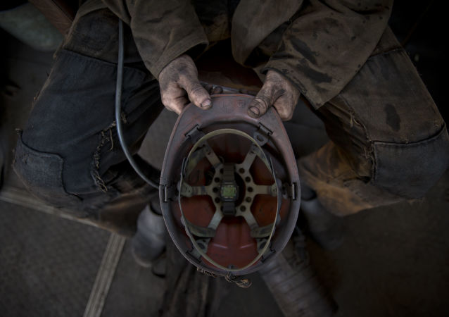 A Ukrainian coal miner holds his helmet after finishing his shift at a coal mine outside Donetsk, Ukraine