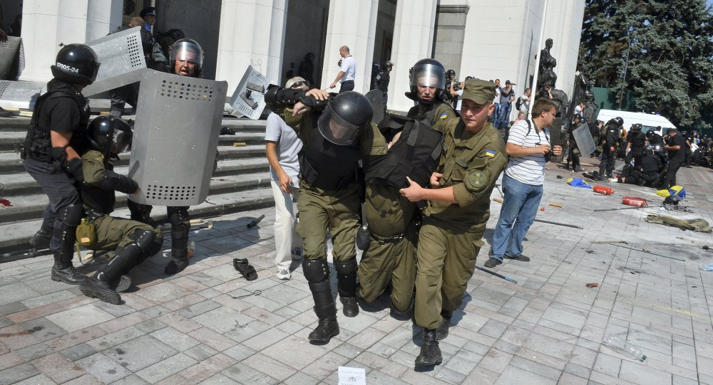 Ukrainian national guard officers carry an injured colleague to an ambulance outside the parliament building in Kiev, Ukraine, August 31, 2015
