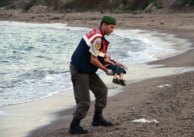 A paramilitary police officer carries the lifeless body of child, lifting it from the sea shore, near the Turkish resort of Bodrum, Turkey, early Wednesday, September 2, 2015.