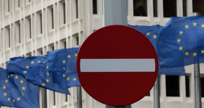 In this photo taken on Monday, March 30, 2015 EU flags flap in the wind behind a no entry traffic sign in front of EU headquarters in Brussels