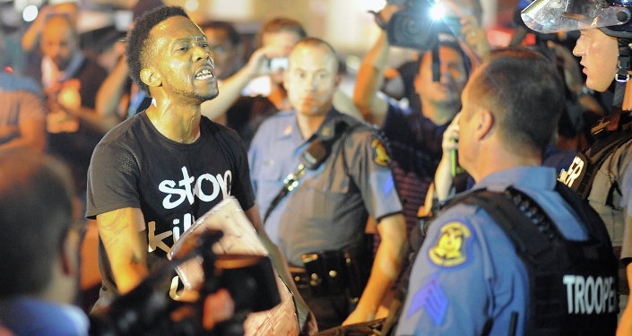A protester (L) speaks emotionally at a police officer during a protest down a street in Ferguson, Missouri