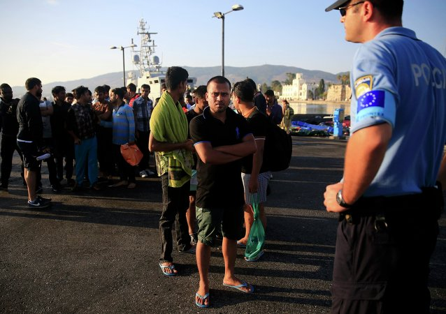 A migrant waits in line next to a Frontex officer (R) at the port of Kos, following a rescue operation off the Greek island of Kos, August 14, 2015