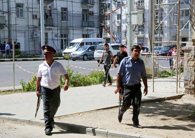 Police officers secure an area in the capital of Tajikistan, Dushanbe, where several Interior Ministry special forces officers and a traffic policeman were reportedly shot dead earlier on Friday, Sept. 4, 2015