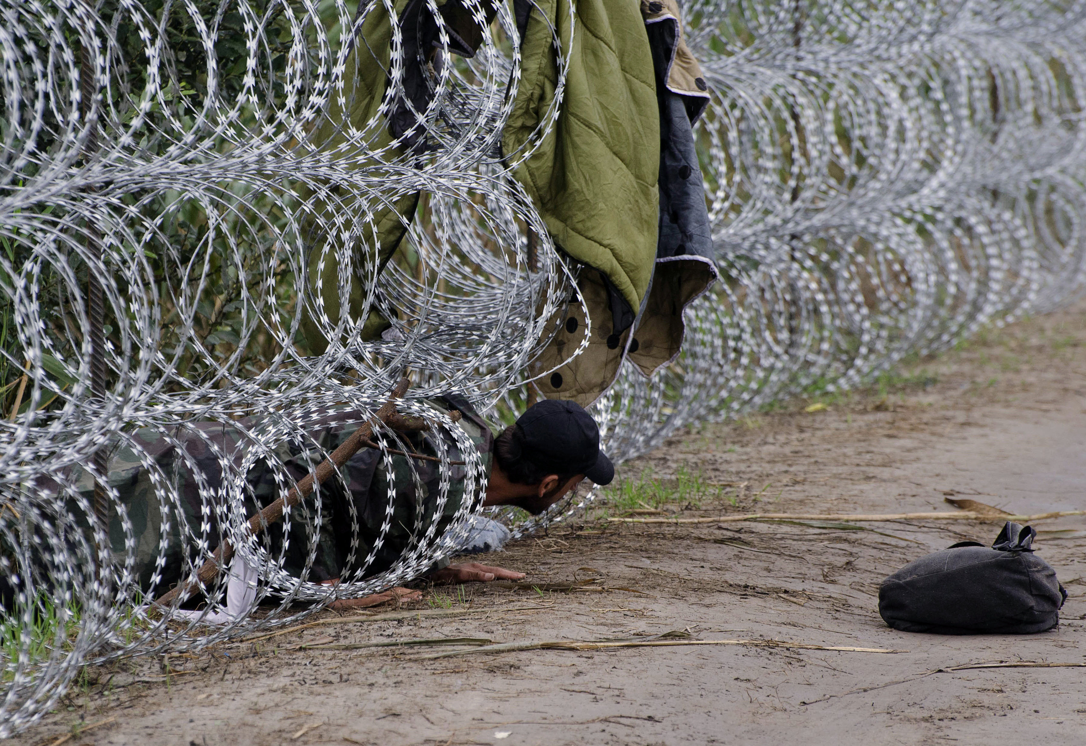 A migrant man creeps under the metal fence near the village of Roszke, at the Hungarian-Serbian border on August 26, 2015