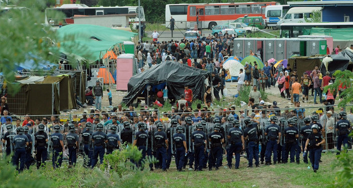 Police officers guard a local refugee camp in the village of Roszke at the Serbian-Hungarian border on September 4, 2015 where migrants are being held.