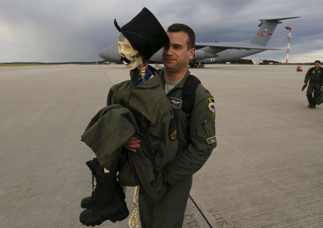 Eric Kordus, a F-22 Raptor fighter jet pilot of the 95th Fighter Squadron from Tyndall, Florida, carries Mr. Bone, the squadron's mascot consisting of a dressed-up plastic skeleton with a stovepipe hat and a moustache, after a refuelling mission of a KC-135 Stratotanker from the NATO airbase of Aemari, Estonia to Spangdahlem, Germany September 4, 2015