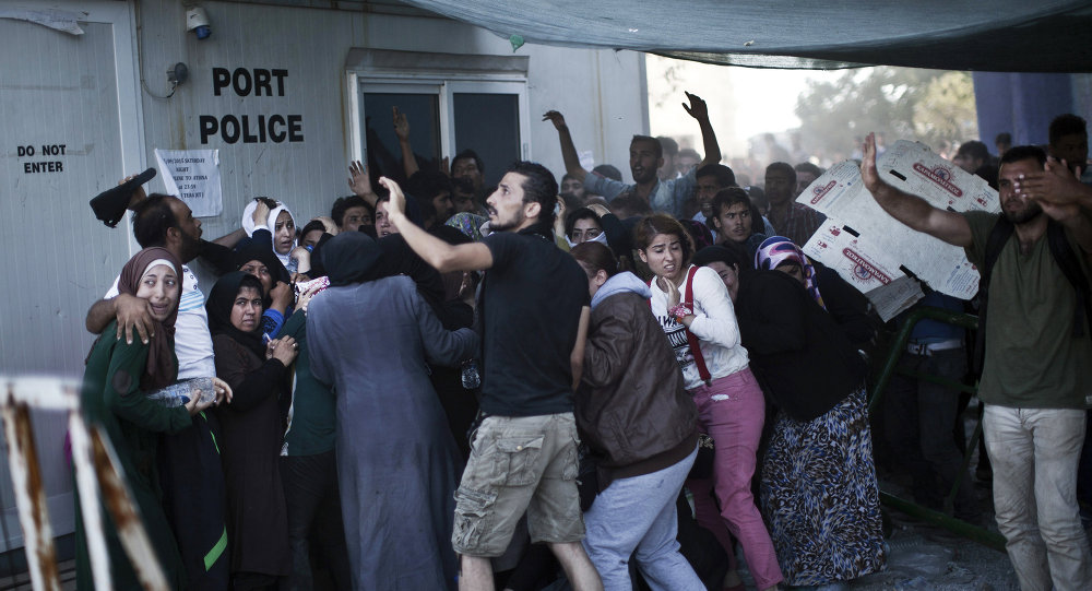 Migrants try to protect themselves from stones as Afghans and Syrian migrants scuffle over priority at a registration queue at the port of Mytilene on the Greek Aegean island of Lesbos on September 6, 2015