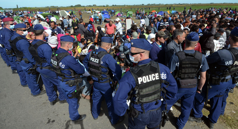 Migrants are controlled by police officers at a refugee collection point near the Hungarian-Serbian border of Roszke village on September 7, 2015