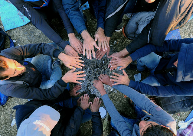 Refugees warm up their hands over hot ash from a bonfire at migrant collection point near Roszke village of the Hungarian-Serbian border on September 8, 2015